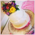 rustic frosted cake , airbrushed gold at the bottom of the tier, fresh flowers were added by the florist.